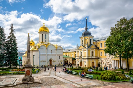 Sergiyev Posad, Russia - August 30, 2012: Pilgrims and tourists in the main square at Holy Trinity St. Sergius Lavra. Unidentified people present on picture. Copy space in blue sky.