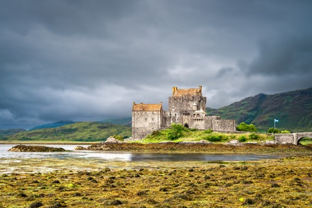 Dornie, Scotland, United Kingdom - August 3, 2018: View from South of iconic Eilean Donan Castle during overcast weather.
