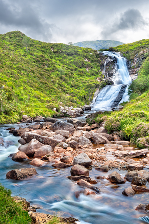 View of Blackhill waterfall on isle of Skye. Copy space on grass and sky.