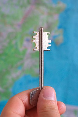 man holding a key on the background maps