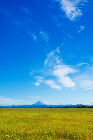 The meadow with the grass against the sky and the volcano in the distance