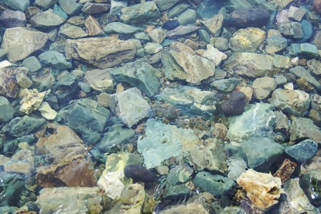 Scattering of stones near shore, not deep under water