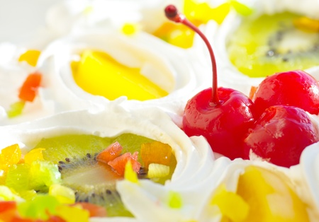 holiday cake decorated with cherries, orange slices and kiwi, close-up, dof