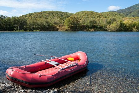 Tourist raft moored on the bank of a mountain river in anticipation of loading supplies and tourists Stock Photo