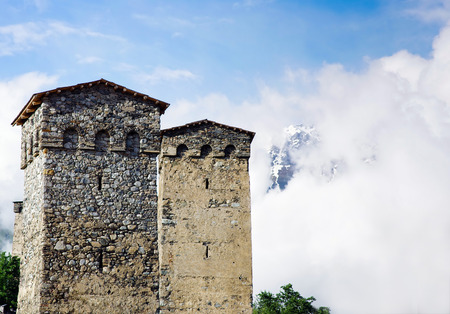 an ancient watchtower in the background of the misty mountains as a symbol of Upper Svaneti, Georgia.