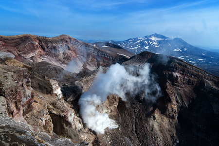 a view from the top edge of the volcanic crater of the volcano Gorely, and the neighboring volcano Mutnovsky