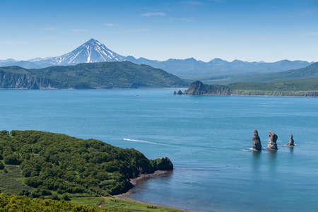 view of the gulf of the Pacific Ocean, the cliff Three Brothers and the hill Vilyuchinsky volcano in the background. Kamchatka Peninsula, Russia