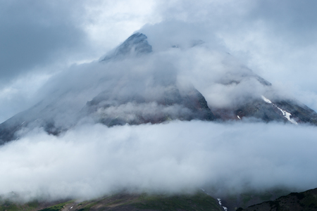 A view of the gloomy peak of an extinct volcano, enveloped in fog and mystery