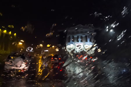 illuminated buildings of the night city through the streams of rain through the car glass