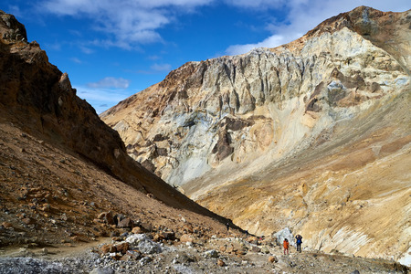 Walking route in the crater of the active volcano Mutnovsky on the Kamchatka Peninsula. Tourists photograph picturesque internal slopes of the crater of the Mutnovsky volcano
