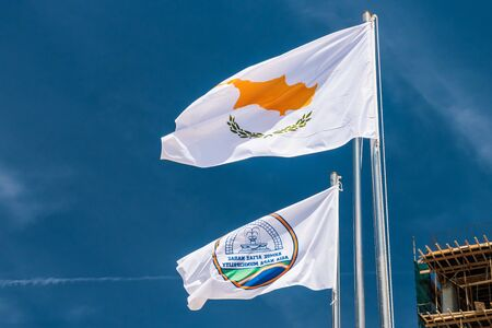 The flag of Agia Napa municipality and the flag of Cyprus. Flags on the flagpole and the stereet lamp post. The wind inflates the flag.
