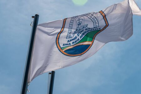 The flag of Agia Napa municipality. Flag on the flagpole and the stereet lamp post. The wind inflates the flag. Banco de Imagens