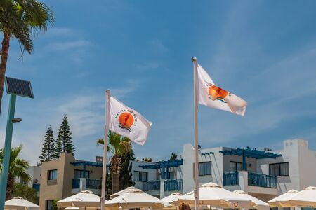 AGIA NAPA, CYPRUS - MAY 26, 2019: Marismare Hotels flags flattering by wind on flagpole stands before hotel building