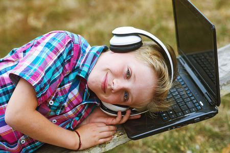 dj boy: Boy listening to music in the city with a laptop Stock Photo