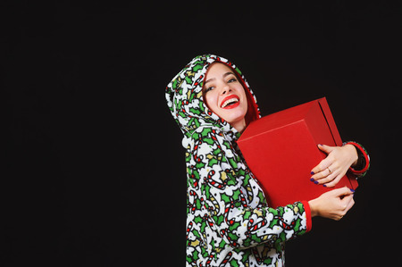 A truly sweet girl with a gift. Woman holding a red box on a dark background, dressed in a ridiculous fancy clothes Stock Photo