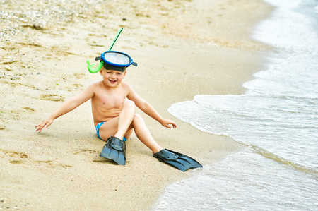 flippers: little boy posing on the beach wearing snorkeling equipment. On the background of the sea