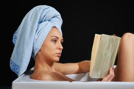 taking bath: girl reading a book while taking bath