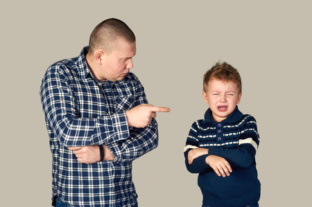 lecturing: father punishes son . Education . On a gray background