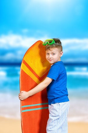 boardshorts: beautiful boy with a surfboard . The dream of tropical countries