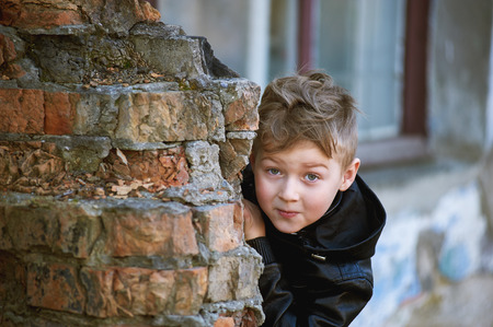 A boy looks out from behind a corner . Kids games