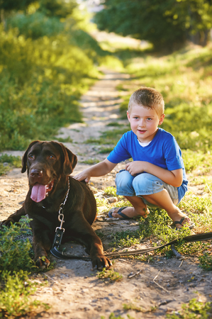 Boy walking with a Labrador Stock Photo