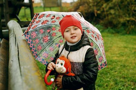 stuff toy: Sad boy in the rain holding a soft toy