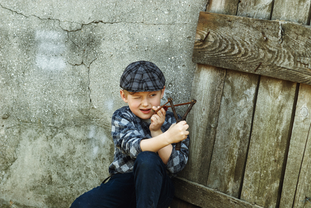 the little boy in the cap , the bully with a slingshot in the hands