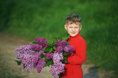 portrait of a boy with a bouquet of lilac Stock Photo