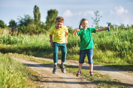 children play with a skipping rope on a summer evening