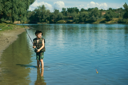 freshwater fish: Boy catches fish in the river.The concept of tourism and leisure Stock Photo