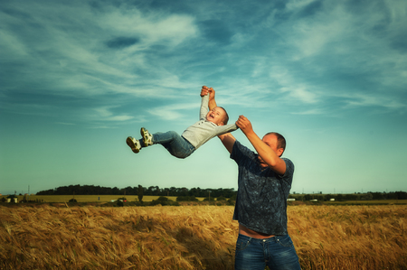 Father playing with daughter in the box , tossing it .Happy family concept