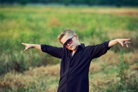 fashionable , stylishly dressed boy posing in nature