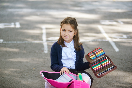 Girl schoolgirl with a backpack and pencils