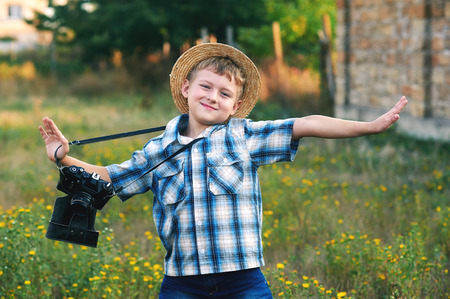 old photo: A little boy with an old camera .Young cheerful photographer