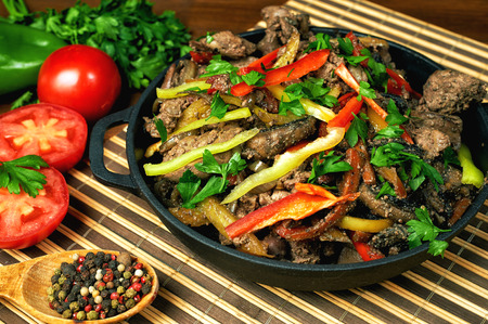 higado de pollo: Fried chicken liver in a cast iron skillet with vegetables Foto de archivo