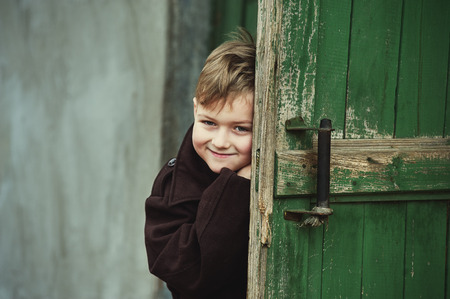 funny boy peeking out from behind the door