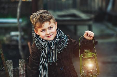 portrait of a boy with a kerosene lamp .Stylish boy holding an old lamp Foto de archivo