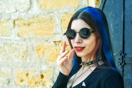 Young girl with blue hair with a cigarette in her hands on the street. Subculture of youth