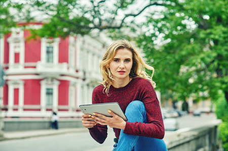 Young woman with tablet on city street . Stylish young woman in jeans and Burgundy sweater uses modern technology