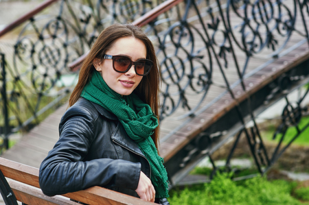 Portrait of a young woman wearing sunglasses in the city .The girl is wearing a leather jacket .Womens casual clothes Stockfoto