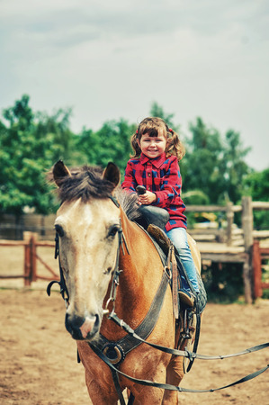 A little girl is trained to ride a horse