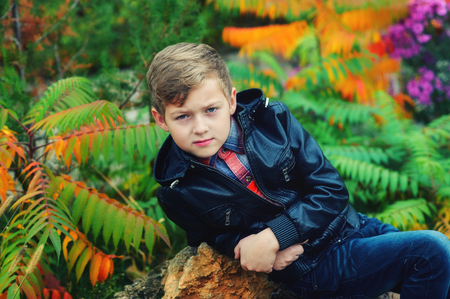 Portrait of a boy in the autumn garden . The boy is wearing a black leather jacket
