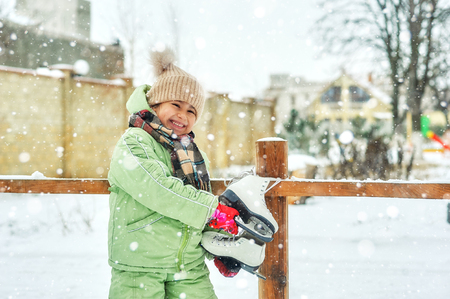 Winter fun in the fresh air . little girl is going to skate outdoors
