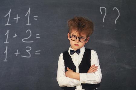 Rozmyślający chłopiec uczeń szkoły podstawowej przy tablicy
