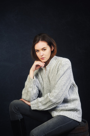 Studio portrait of a young woman on a dark background . The girl is dressed in a warm knitted sweater