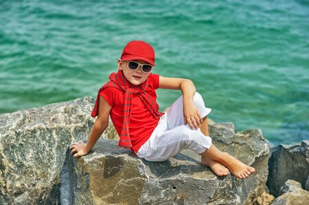 Fashionable handsome boy on the sea coast . Rest and travel . The child sits on a stone in light trousers .