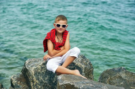 Fashionable handsome boy on the sea coast . Rest and travel . The child sits on a stone in light trousers . Stock Photo