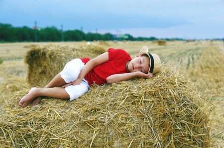 Portrait of a little boy on vacation in the field . The child lying in the manger Banque d'images