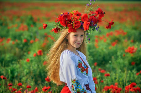 Portrait of a girl in national costume in a field with poppies