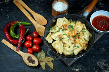 Baked dumplings in a cast-iron pan with onions. The view from the top .Cooking delicious at home Zdjęcie Seryjne